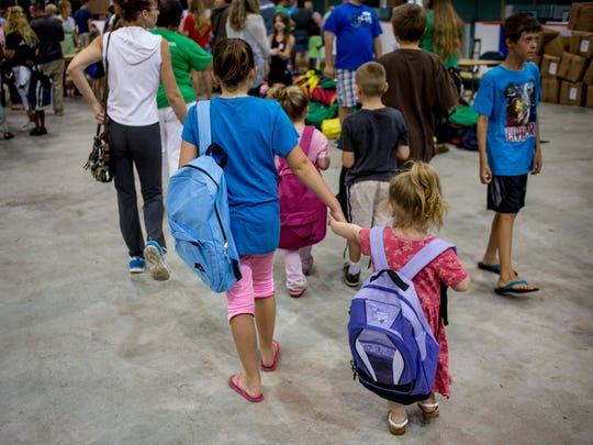 Clara Andrzejewski, 10, holds hands with her sister, Evelyn Farquhar, 3, of Port Huron, as they make their way through a line during the annual backpack giveaway hosted by Blue Water Community Action Wednesday, August 17, 2016 at McMorran Arena in Port Huron.
