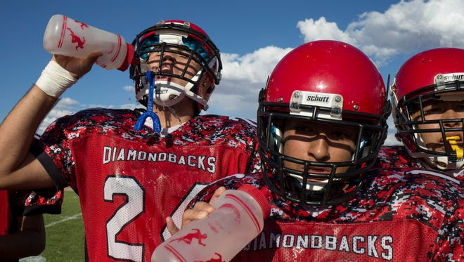 Brandon Gonzales (center) and Arturo Gonzlez (left) get a drink, September 4, 2015, during a timeout in the fourth quarter.