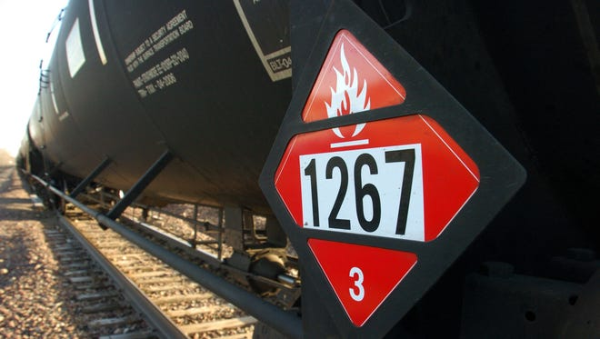 A warning placard on a tank car carrying crude oil is seen on a train idled on the tracks near a crude loading terminal in Trenton, N.D. on Nov. 6, 2013. The transport of oil by rail has expanded more than thirty-fold since 2009, delivering higher prices for oil companies able to access to coastal refineries but also raising concerns about spills. (AP Photo/Matthew Brown)