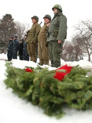 (L to R) World War Two re-enactors Greg Schultz, 47 of Sterling Heights and Chris Causally, 46 of Eastpointe along with Vietnam re-enactor Joe Coppens, 37 of St. Clair Shores, stand listening to speeches during the Wreaths Across America event held at Resurrection Cemetery in Clinton Township on Saturday, December 17, 2016.