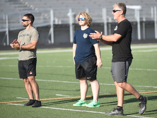 Robert Luther (from left) and Emily Reed from Crossfit Amend and Jerry McDonald of The Racquet Club/Westar Fitness encourage reservists participating in a PT session for the IRT reservists at Bomber Stadium.