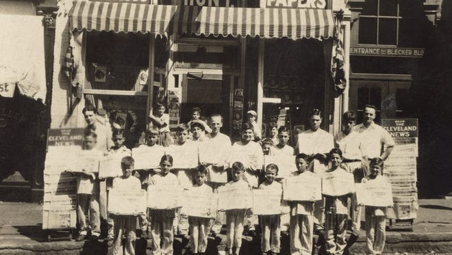 "Fred Hunt, far right, and his newsboys gather in front of his North Main Street newsstand in this undated photo. Look closely and you'll see the boys are all dressed in pajamas, and at the bottom is written ""Hunt's Pajama Hustlers."" It was no doubt a promotion for the Cleveland News, shown prominently on either side. (Photo courtesy of the Mansfield Memorial Museum)"