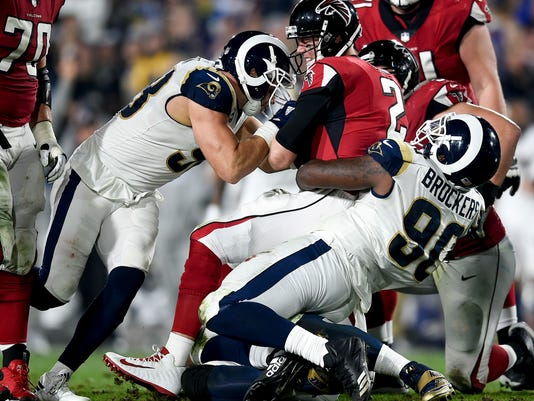 Atlanta Falcons quarterback Matt Ryan, middle, is sacked by Los Angeles Rams outside linebacker Connor Barwin, left, and nose tackle Michael Brockers during the first half of an NFL football wild-card playoff game, Saturday, Jan. 6, 2018, in Los Angeles. (AP Photo/Kelvin Kuo)