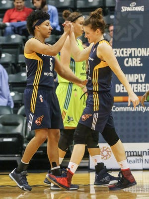 The Indiana Fever's Layshia Clarendon, left, high fives team mate Maggie Lucas after Lucas hit the ground on a play, Sunday May 1st, 2016. The Indiana Fever took on the Dallas Wings in the pre season at Banker's Life Fieldhouse, winning 108-90.