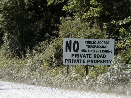 A large sign warns against trespassers and uninvited