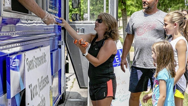 Julie Meek and her family receive orange push popsicles and ice cream sandwiches in the Kitsmiller's Crossing subdivision.