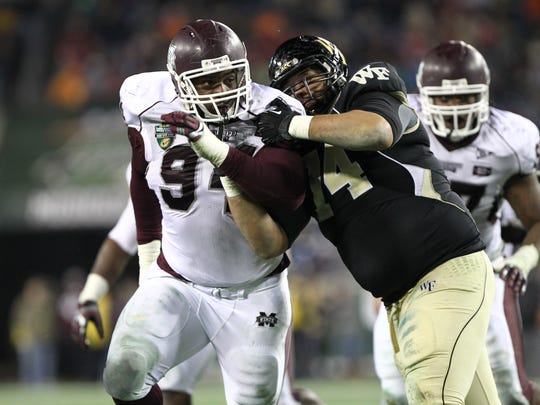 Mississippi State defensive lineman Fletcher Cox is held by a Wake Forest lineman in the second half of the 2011 Music City Bowl.