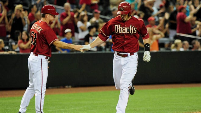 Arizona Diamondbacks first baseman Paul Goldschmidt (44) celebrates with third base coach Glenn Sherlock (53) after hitting a 2 run home run during the seventh inning against the San Diego Padres at Chase Field on May 28, 2014.