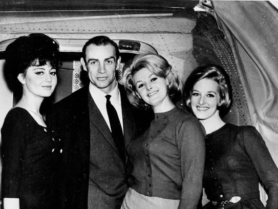 """Actor Sean Connery is flanked by """"Bond Girls"""" while"""