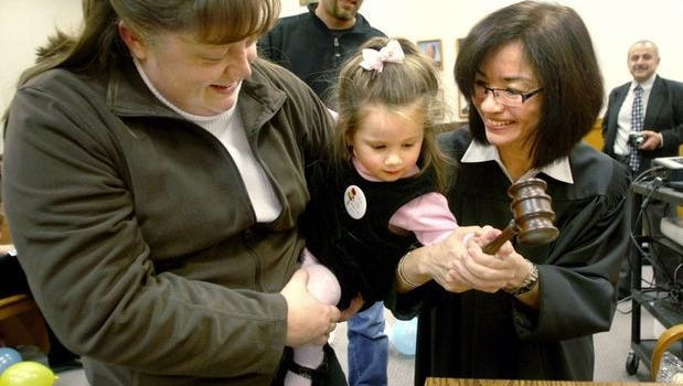 Elizabeth Hicks, left, with the assistance of Judge Leila Mills, helps her newly adopted daughter Lisa, 2, bang the gavel Friday during the 2008 National Adoption Day at the Kitsap County Courthouse.