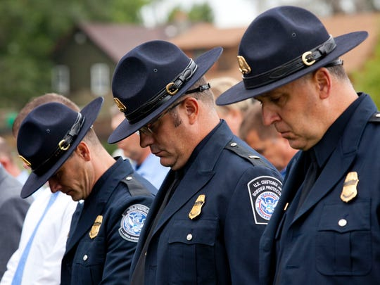Customs and Border Protection officers bow their heads during a 9/11 remembrance ceremony at the International Flags Plaza in Port Huron.