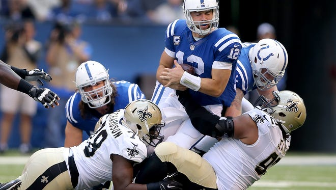 Indianapolis Colts quarterback Andrew Luck (12) is sacked by New Orleans Saints defensive tackle John Jenkins (right) and defensive end Bobby Richardson (left) during the second half of an NFL football game Oct. 25, 2015, at Lucas Oil Stadium, Indianapolis.