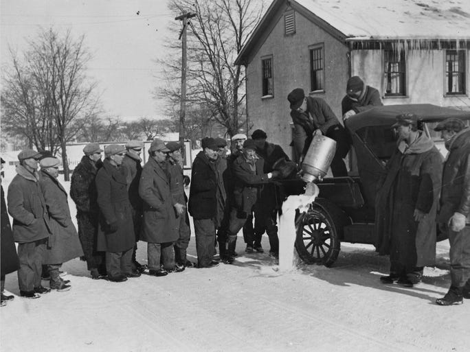 Dairy farmers and their allies dump cans of milk in this undated Milwaukee Journal photo. During 1933, farmers groups staged three milk strikes in Wisconsin in a bid to boost the prices farmers got for milk. The strikes ??? in February, May and October-November ??? sometimes escalated into violence, including crowds being tear-gassed and bayoneted, a couple of strikers being shot and several dairy plants in the state being bombed.