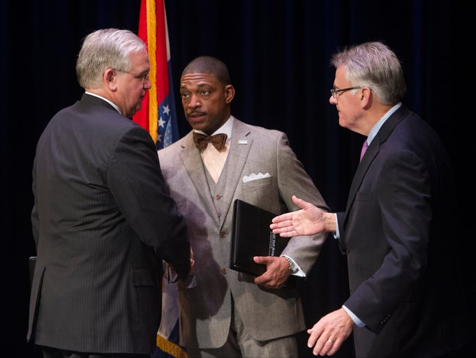 Missouri Gov. Jay Nixon, left, shakes hands with Rev.