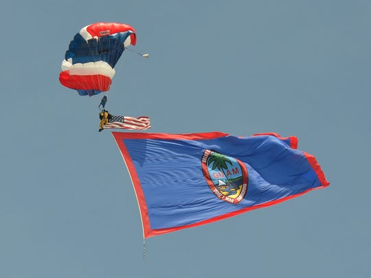 "Retired Army Special Forces Maj. Eutemio ""Tim"" Ohno paracutes down to the 2013 parade grounds flying American and Guam flags at the start of the 69th Liberation Day parade. Round out your weekend fun with the 71st Liberation Day parade."