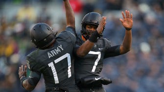 Army Black Knights quarterback Ahmad Bradshaw (17) celebrates in the air with fellow quarterback Chris Carter (7) after a touchdown against the Navy Midshipmen during the first half at M&T Bank Stadium.