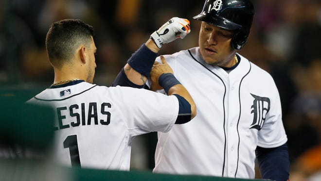 Tigers shortstop Jose Iglesias squeezes first baseman Miguel Cabrera's arm at the dugout steps after Cabrera hit a two-run home run scoring Rajai Davis in the fifth inning of the Tigers' 5-0 win Wednesday at Comerica Park.