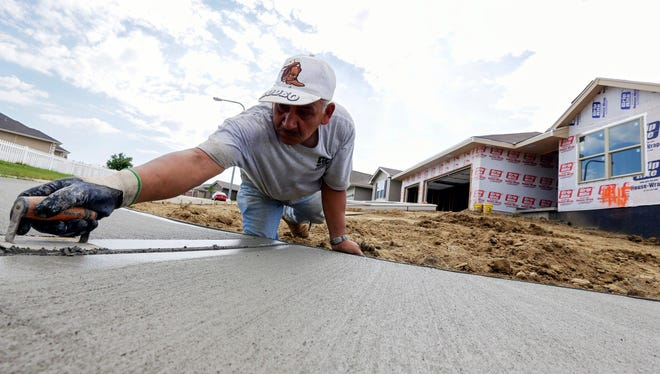 A sidewalk gets shaped in front of new home construction in Omaha, Neb.