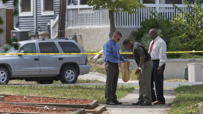 Police collect possible evidence at crime scene on First Avenue near its intersection with Central Avenue in Asbury Park Thursday.