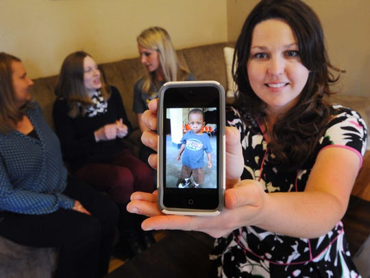 AmyJon Hibbert, Fishers, holds her phone showing a photo of her adopted son Isaac, 2, who is still in the Congo.  Behind her sit Ronda Haston (from left), Heather Long and Amanda Larner, all adoptive mothers of children from the Congo waiting for an exit letter from the Congo government to be able to bring their children to Indiana.