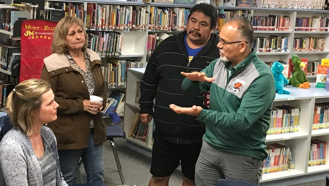 Ernie Flores, middle, speaks to parents and staff after learning his contract won't be extended and was placed on administrative leave. The board will look for a new superintendent.