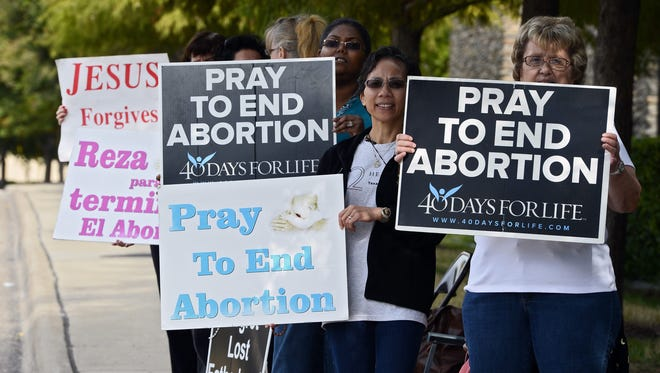 Protesters stand with signs along the street in front of Southwestern Women's Surgery Center in Dallas on Tuesday.