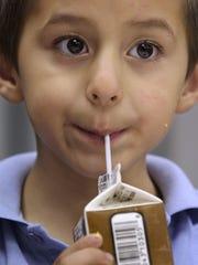 Santiago Fernandez, 5, drinks his milk during lunch