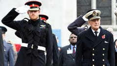 Harry, left, salutes as he stands alongside his grandfather Britain's Prince Philip, Duke of Edinburgh, during their visit to the Field of Remembrance at Westminster Abbey in central London on Nov. 10, 2016.