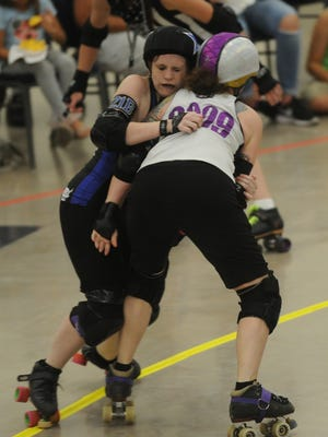 Abilene jammer G.G. Ellin, left, tries to get around North Texas' Felonious Flingin Monkey during a jam during their June 24 game at the Abilene Convention Center. The North Texas Mermaids beat the Sugarbombs, 145-130.