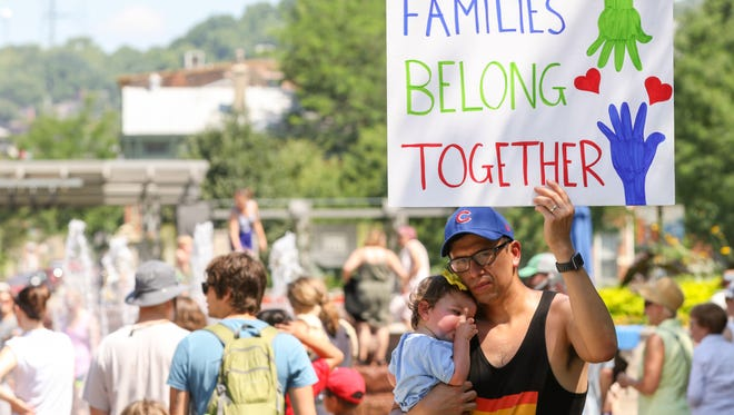 Kyle Umlang holds up a sign while holding his one-year-old daughter, Wesley, at the Families Belong Together March at Washington Park in Over-The-Rhine, Cincinnati, on Saturday, June 30, 2018.
