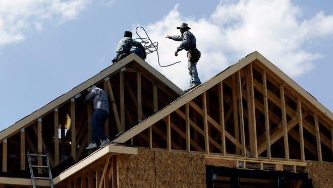 Workers help build a house in San Antonio in 2012. Texas annually attracts more new residents from other states than any other state.