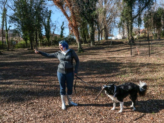 Ana Mieka, left, and border collie Louie walks in the area on Friday, where TBA Dog Park along Fant Street is not completed.