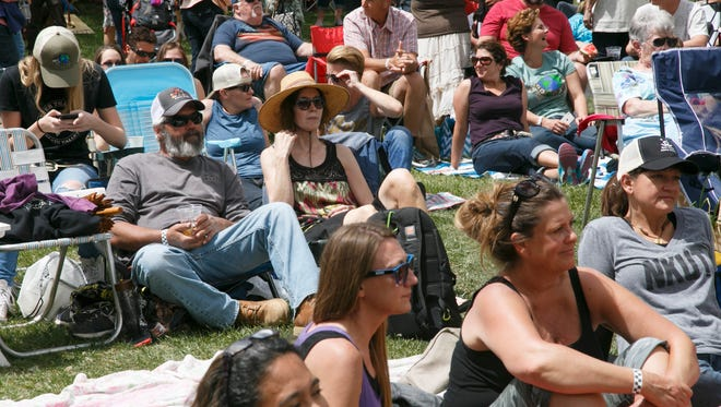 Spectators sit on the lawn outside of the Bit and Spur in Springdale while the band Home Early on Sunday performs on the outdoor stage during Springdale's Earth Day festival Saturday, April 23, 2016.