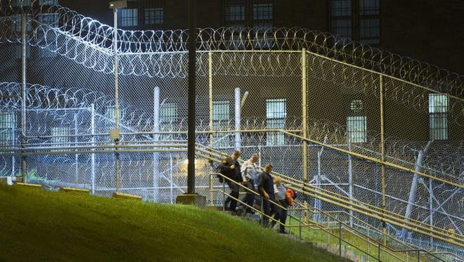 In this June 15, file photo, corrections officers walk next to a fence covered in razor wire as they leave work at Clinton Correctional Facility in Dannemora, N.Y. The June 6 escape by David Sweat and Richard Matt spotlighted apparent security lapses in the prison.