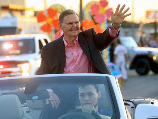 Mayor-elect Joe McComb waves at a crowd as he participates