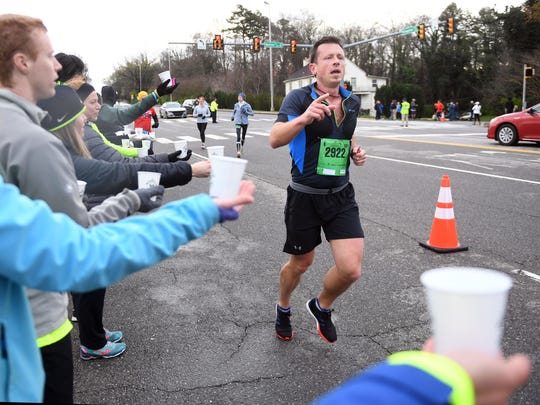 Ben Mills runs past the water station on Kingston Pike