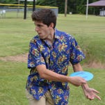 Southern Miss student Derek Cunningham throws his frisbee into the Disc Golf basket at Tatum Park on Wednesday.