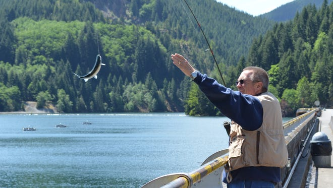 Frank Kuhr of Salem lands a trout off the dam at Detroit Lake, which will be stocked in advance of the Detroit Lake Fishing Derby.