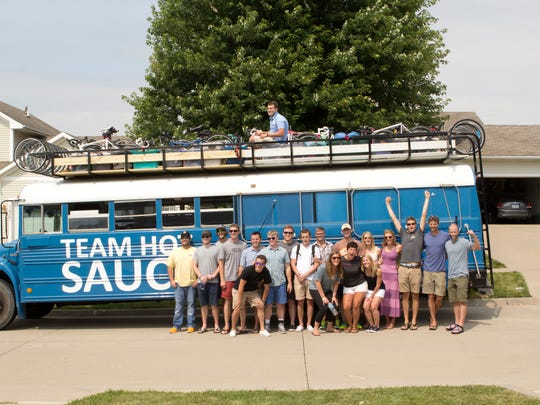 Members of Team Hot Sauce pose for a photo in front of their blue bus. Charlie Cutler has his arms raised in the air.
