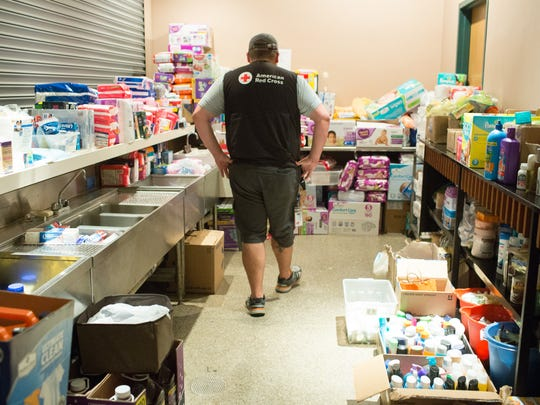 This Advertiser file photo shows a volunteer looking over supplies at the Red Cross shelter at the Heymann Center in Lafayette.