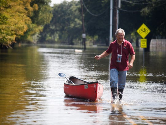 Bayou Vermilion District  CEO David Cheramie pulls a canoe through a flooded Fisher Road outside Vermilionville  August 25, 2016.