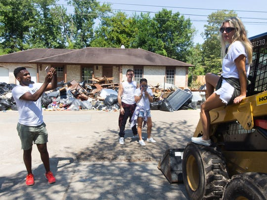 """Justin Sylvester of """"Rich Kids of Beverly Hills""""  takes a photo of fellow cast member Morgan Stewart as they tour the flood-damaged  East Bayou neighborhood of Lafayette September 2, 2016."""