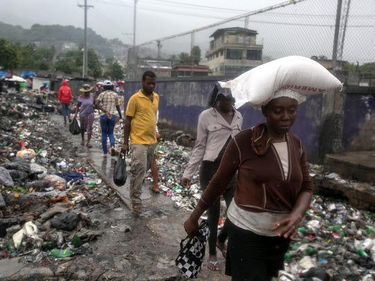 Residents walk through a garbage filled street in Port-au-Prince, Haiti, on Oct. 4, 2016.