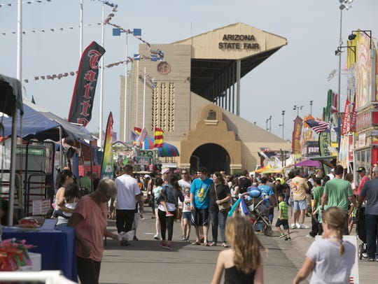 Fair goers walk the streets of the Arizona State Fair