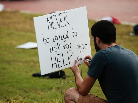 Logan Viator writes a sign Wednesday in the quad of UL Lafayette during Send Silence Packing, an event to raise awareness of suicide among college students.