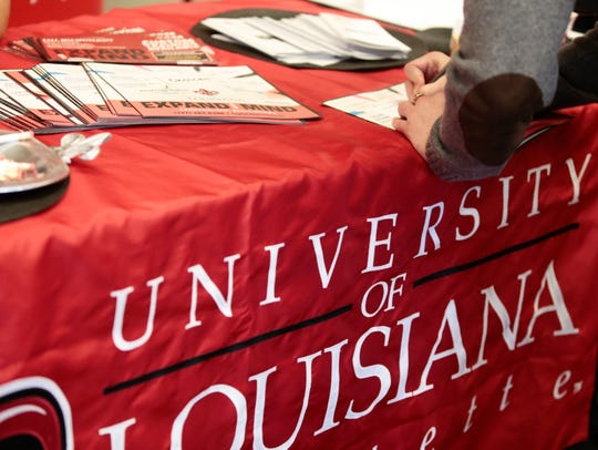 An attendee signs a form at the UL Lafayette booth