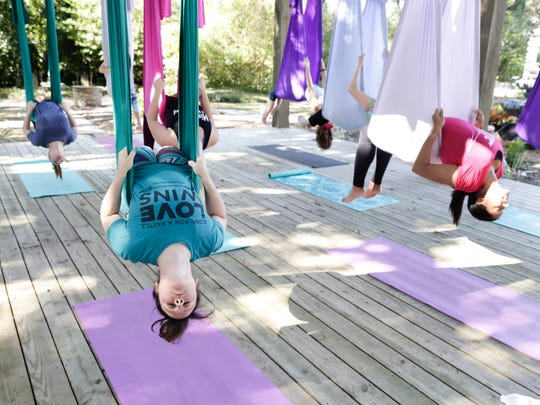 Sarah Thibodeaux, in green, takes part in a yoga class incorporating hanging silksOct. 29, 2016 at Yoga Garden in Lafayette.