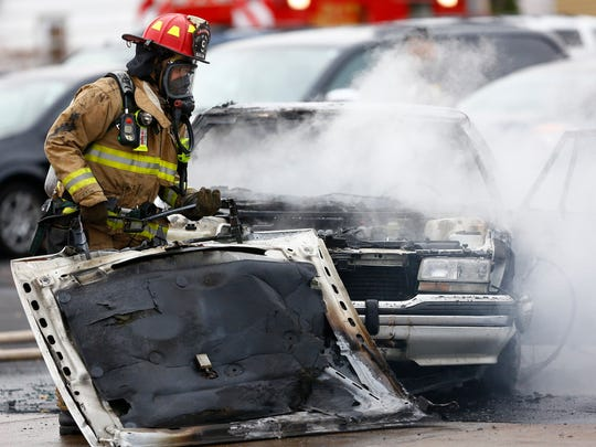A Wausau firefighter drags a hood from a vehicle that caught on fire Monday morning at a parking lot near Eastbay on First Avenue in Wausau.