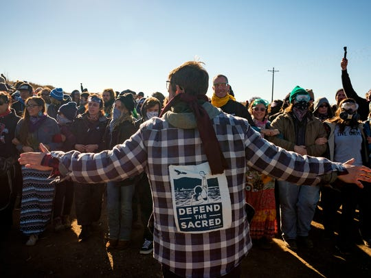 A Dakota Access Pipeline protester leads more than