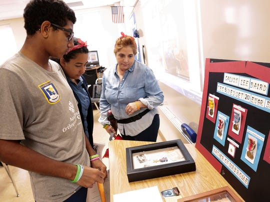Teacher Vickie Hebert, right, looks at a World War II soldier's memorabilia with students during a 1940s symposium at South Louisiana Community College's Early College Academy in Lafayette Nov. 15, 2016.